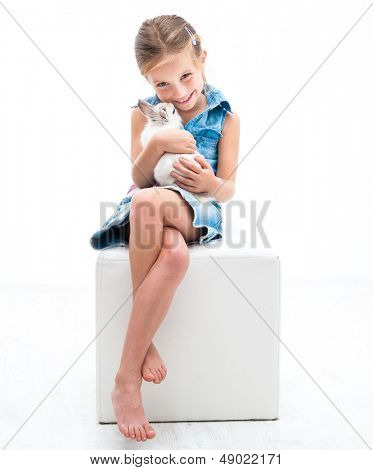 caring little girl in denim clothing playing with white rabbit poster