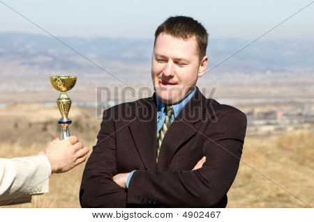 Businessman Screwing Up His Eyes At Golden Cup