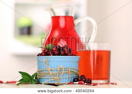 Pitcher and glass of cranberry juice with red cranberries on table