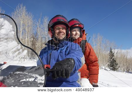 Happy couple sitting on snowmobile in snow