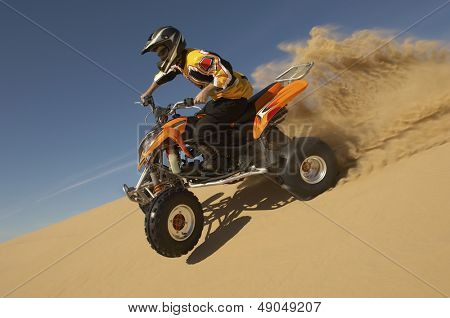 Low angle view of a man riding quad bike in desert against the blue sky