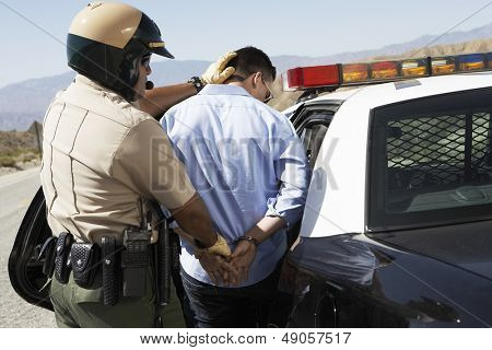 Rear view of a police officer guiding apprehended man into police car