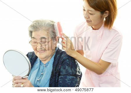 Friendly nurse cares for an elderly woman