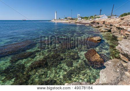 Lighthouse, sea and rock, blue sky. Crimea.