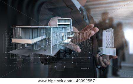 Businessman Hand Presents House Model On Modern Computer