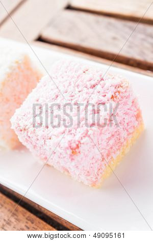 Pink Lamington Cakes Up Close On Wood Table