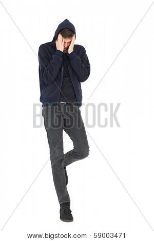 Full length of a cool young man with headache over white background