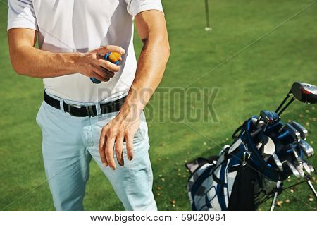 Golf sport man with sunblock lotion spray for spf protection poster