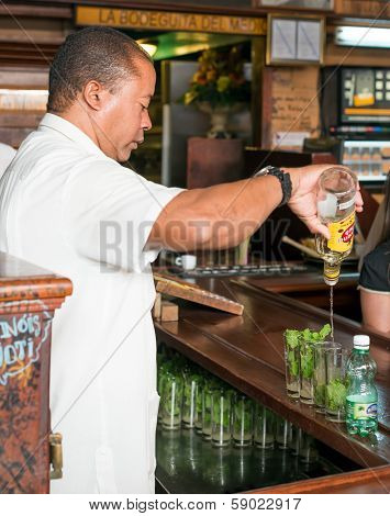 HAVANA,CUBA - JANUARY 20, 2014: Bartender preparing mojitos at La Bodeguita del Medio.This famous restaurant was a major attraction for the almost 3 million tourists who visited Cuba in 2013