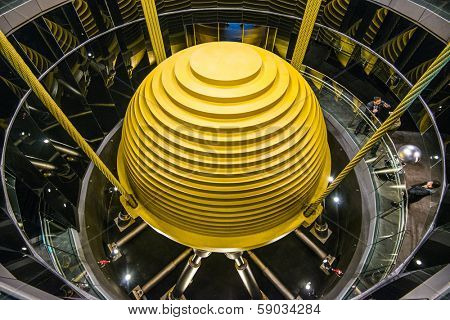 TAIPEI, TAIWAN - JANUARY 15, 2013: Tourists observe the world's largest tuned mass damper in Taipei 101. The device is used to reduce unwanted vibration from wind and earthquakes.