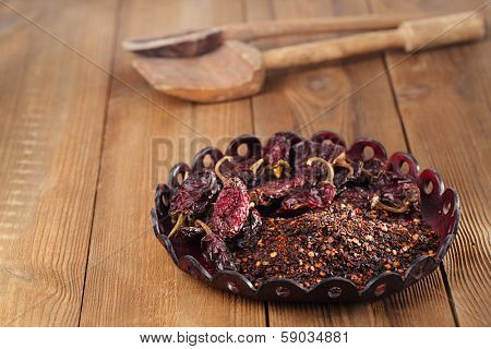chipotle - jalapeno smoked chili flakes and whole in leather bowl,  shallow dof poster