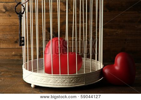 Hearts in decorative cage on wooden background