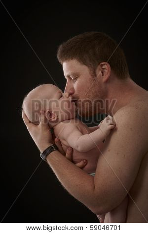 Father holding and kissing newborn baby, semi-nude, side view.