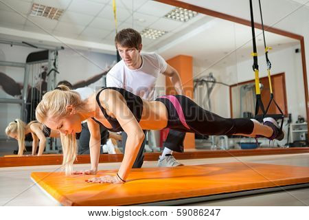 girl doing pushups with resistance band in the presence of a personal trainer poster