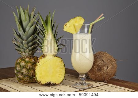A Pina Colada a half of a pineapple and a coconut are standiing on a tabletop of acacia wood. The background is gray. poster