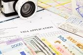 closeup visa application form passport camera and world currency. planning schedule for holiday and vacation poster