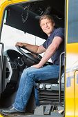 Logistics - proud driver or forwarder in drivers cap of truck and trailer, on a transshipment point poster