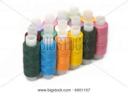 Spools of different color sewing threads isolated on white background
