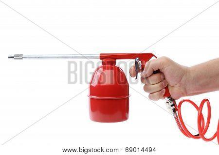 Hand holds spray gun with plastic spring.