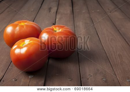 Three Tomatoes On Brown Table With Copy Space