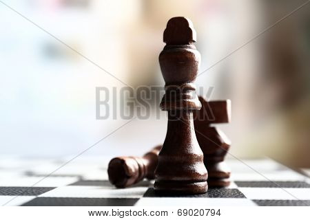 Chess board with chess pieces on light background