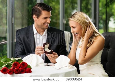 Man holding box with ring making propose to his girlfriend