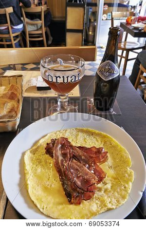 Orval Trappist Belgian Ale Bottle And Glass On A Table With Bacon And Eggs
