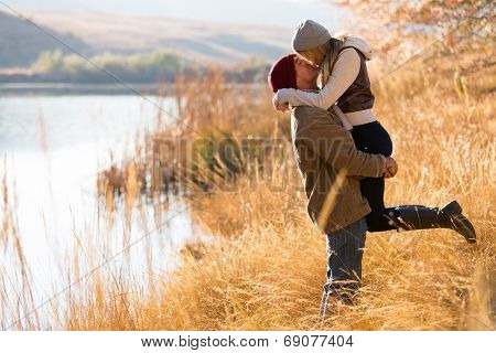 lovely young couple kissing outdoors in autumn