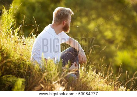 Happy Man Sitting On The Grass
