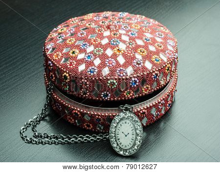 Old indian jewelery box with old watch on a chain. A wooden background. poster