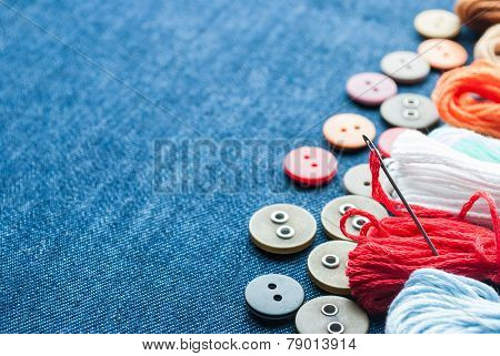 Closeup blue jeans background with different buttons and threeds. Space for your text.