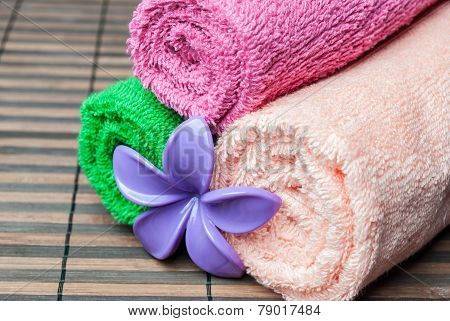 Closeup spa towels rolls and flower lying on wooden mat. Horizontal composition.
