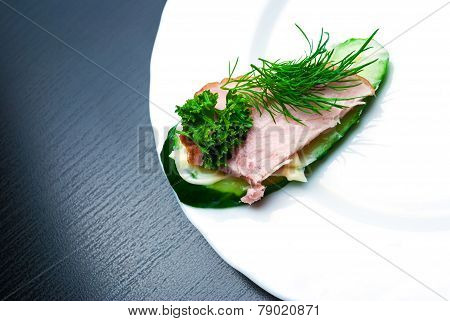 Closeup of delicious ham and cucumber canapes sandwiches with parsley lying on a white plate. ** Note: Shallow depth of field