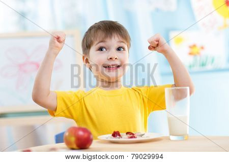 child boy eating healthy food and showing his strength