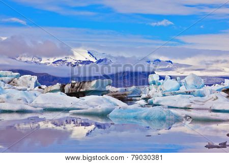 Icebergs and ice floes  of freakish forms are reflected in smooth water.  Iceland in July. Ocean ice lagoon Yokulsarlon