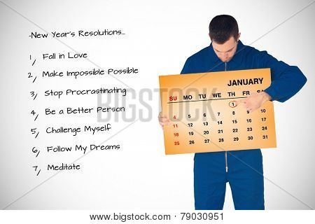 Young mechanic in boiler suit pointing on calendar in his hands against orange card