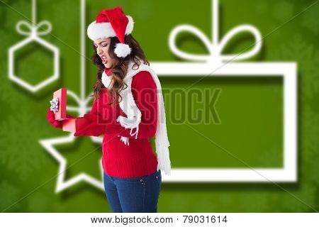 Disgusted brunette opening christmas gift against blurred christmas background