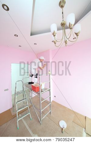 Plasterer with spatula in hand standing on scaffolding in pink room
