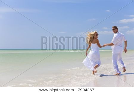 Happy Young Couple Running Holding Hands On A Tropical Beach