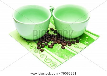 Two cups of green standing on a tissue with coffee beans isolated on white.