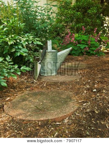 Portrain Orientation Of A Trowel And Watering Can On The Garden Path