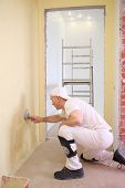 Builder sitting on the floor inflicts the plaster on the wall using a pallet poster