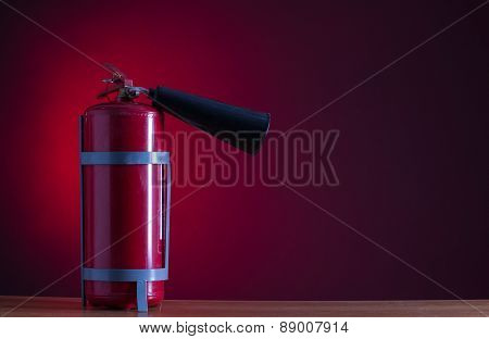 Fire extinguisher on a red background.