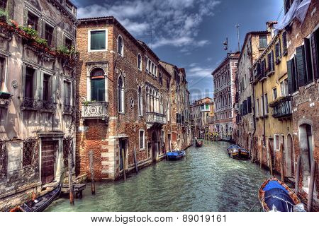 Boats & Gondola down a street canal off the Grand Canal in Venice, Italy