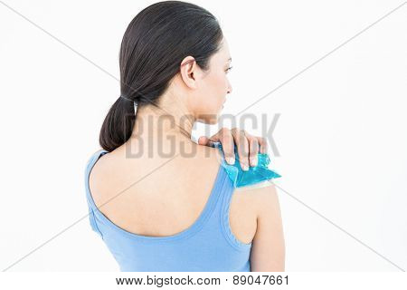 Beautiful brunette putting gel pack on shoulder on white background