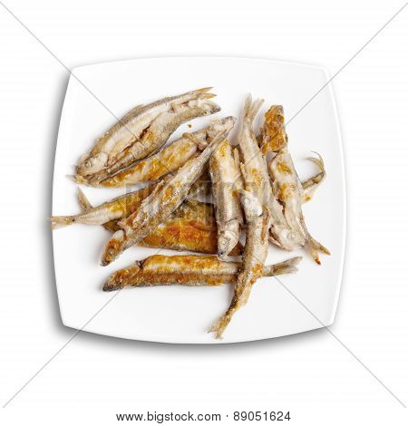 Pile Of Fried Smelts Fish Lays On A White Plate, Top View Isolated On White