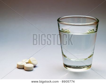 A white medicine pill with water glass