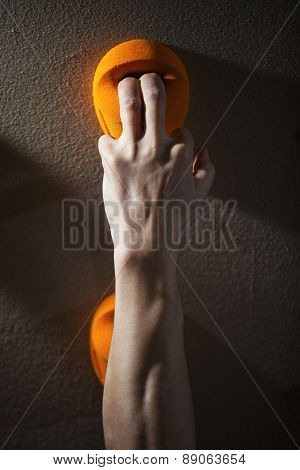 Rock climber gripping handhold with two fingers