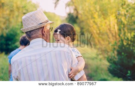 Back view of senior man holding baby girl in his arms