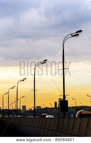 Sunset Over Big City Road. Perspective Line Of Streetlamps.